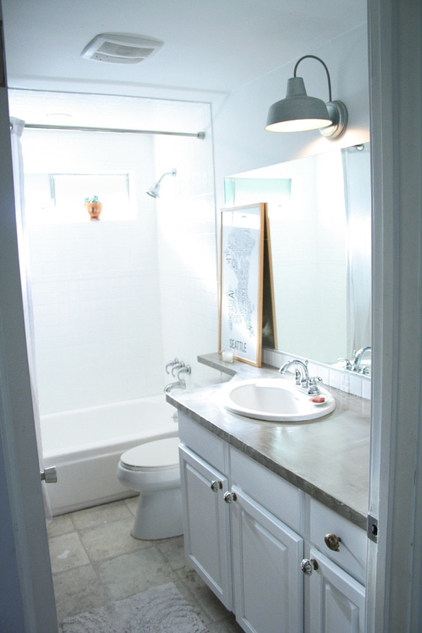 Concrete counters, painted shower tile, barn light, white cabinets