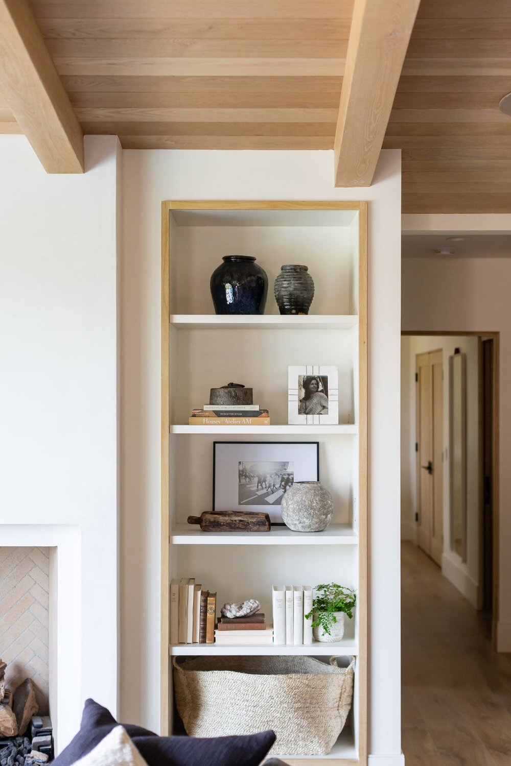 wood ceiling beams with wood trimmed built in cabinet and matching wood floors
