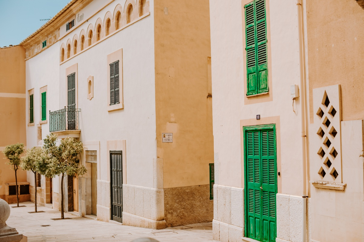 Alcudia architecture with green shutters and pink sandstone buildings